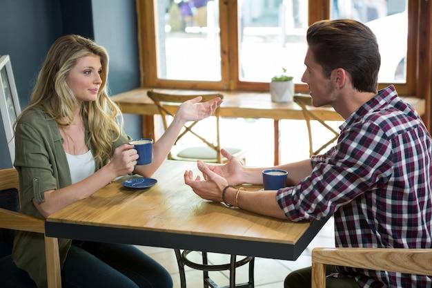 Jeune couple, parler, quoique, avoir café, table, dans, café