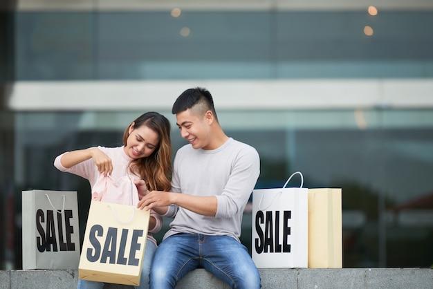 Jeune couple partageant des achats en vente