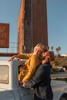 Jeune couple partageant des moments tendres lors de leur voyage en voiture