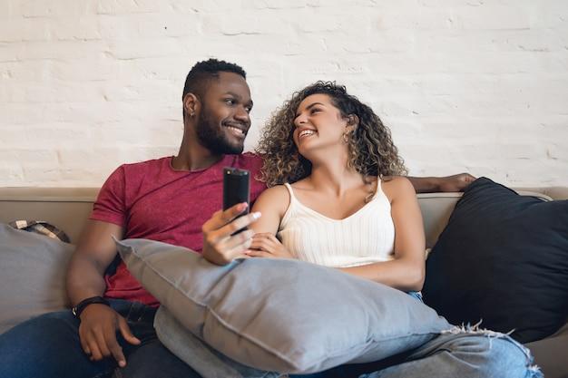 Jeune couple passant du temps ensemble et regardant des séries télévisées ou des films assis sur un canapé à la maison.
