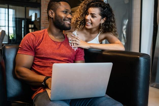 Jeune couple passant du temps ensemble tout en utilisant un ordinateur portable à la maison. nouveau concept de mode de vie normal.