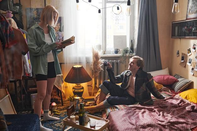 Jeune couple passant leur temps ensemble à la maison jeune femme lisant un livre et homme assis sur le lit et buvant de l'alcool