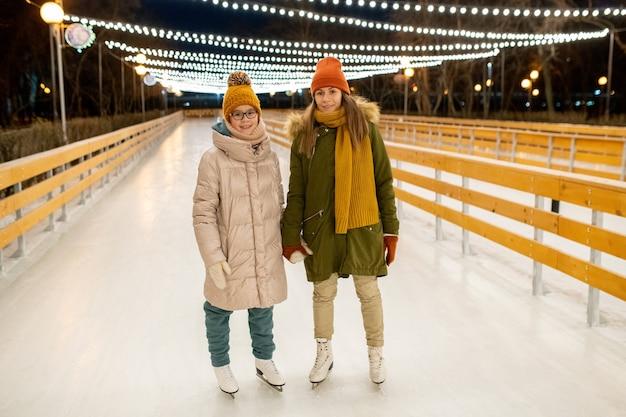 Jeune couple passant leurs vacances de noël sur une patinoire dans le parc