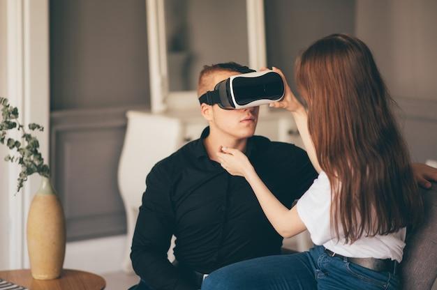 Jeune couple passe du temps ensemble à jouer à la réalité virtuelle dans le salon