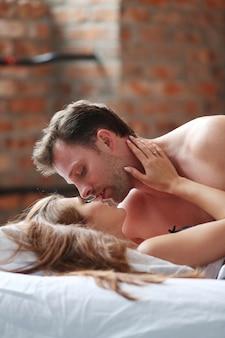 Jeune couple passionné au lit
