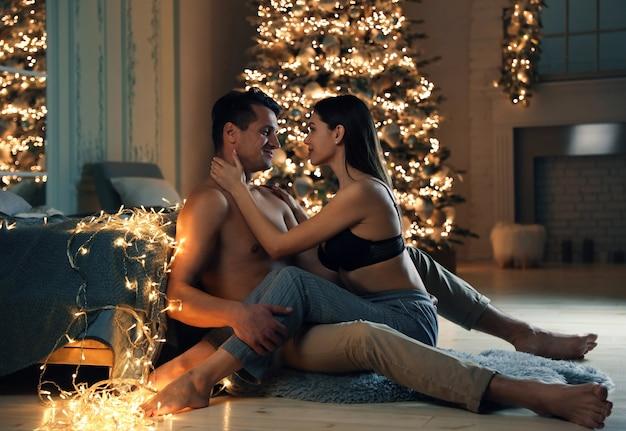 Jeune couple passionné s'appréciant dans la chambre décorée pour noël