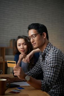 Jeune couple payant avec carte de crédit en ligne
