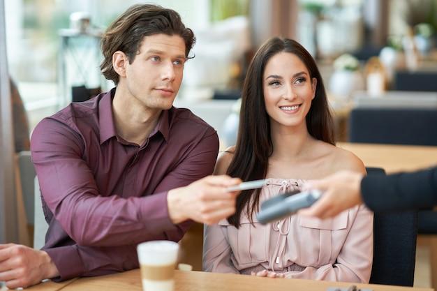 Jeune couple payant par carte de crédit au café