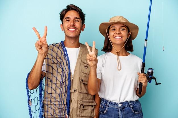 Jeune couple de pêcheurs de race mixte isolé sur fond bleu montrant le numéro deux avec les doigts.