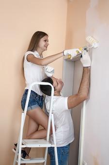 Jeune couple peignant un mur à la maison avec un rouleau et s'entraidant. elle est sur l'échelle.