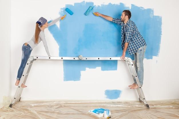 Jeune couple peignant des murs dans un nouvel appartement