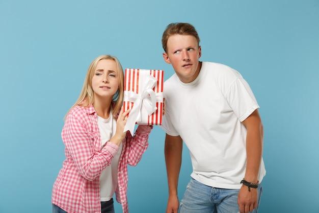 Jeune couple pensif deux amis gars et femme en t-shirts roses blancs posant