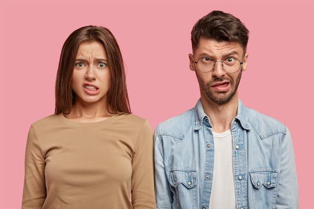 Jeune couple perplexe posant contre le mur rose