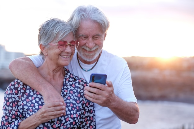 Jeune couple de personnes âgées embrassant en plein air en mer au coucher du soleil à l'aide de téléphone portable de race blanche