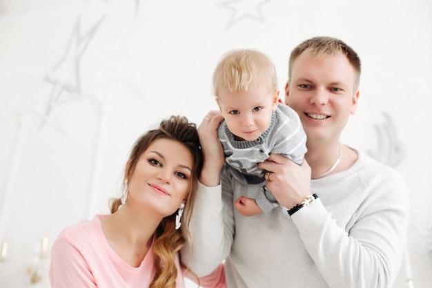 Jeune couple avec petit fils debout dans le studio de noël, regardant avant et posant