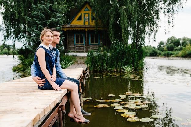 Le jeune couple pieds nus assis sur un pont en bois au-dessus du lac