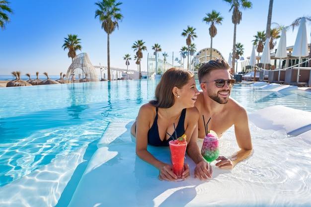 Jeune couple sur la piscine à débordement avec des cocktails
