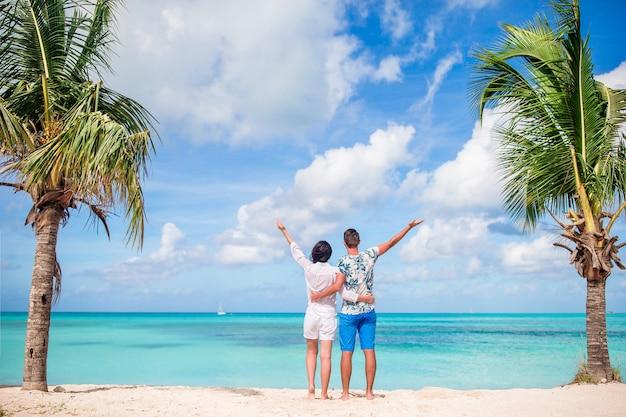 Jeune couple sur la plage blanche. famille heureuse en vacances de lune de miel