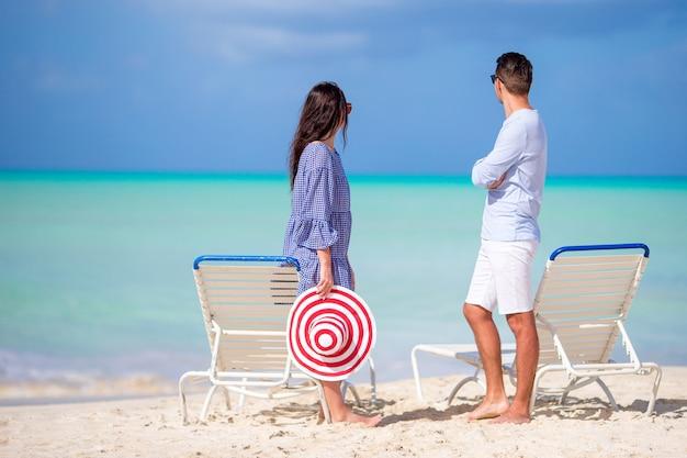 Jeune couple sur une plage blanche pendant les vacances d'été. happy family profiter de leur lune de miel