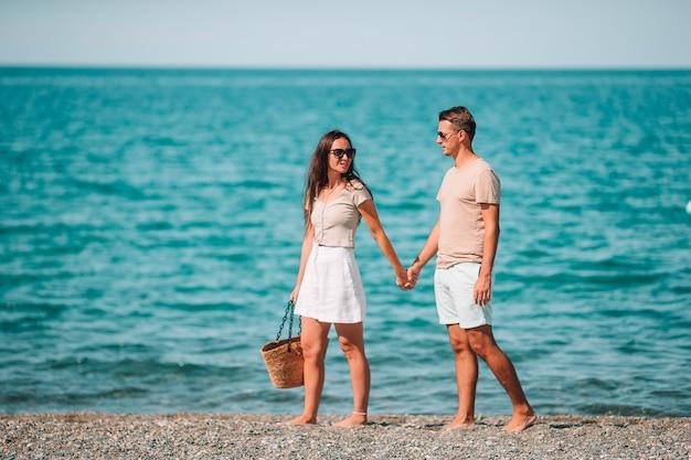 Jeune couple sur la plage blanche pendant les vacances d'été