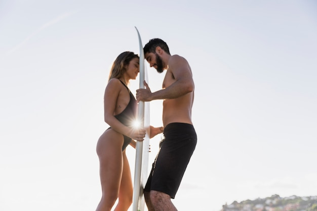 Jeune couple avec planche de surf sur ciel nuageux