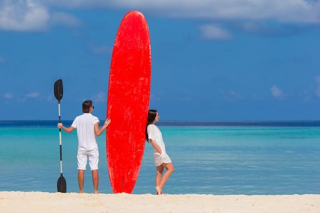 Jeune couple avec planche de surf rouge pendant des vacances tropicales