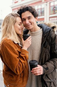 Jeune couple en plein air appréciant une tasse de café