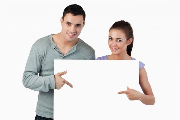 Jeune couple pointant sur la bannière en face d'eux
