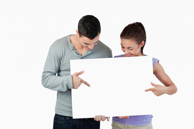 Jeune couple pointant sur la bannière qu'ils présentent