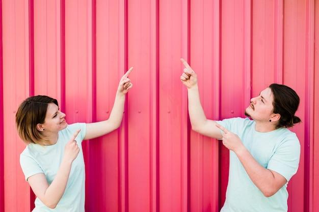 Jeune couple en pointant son doigt vers le haut contre la tôle ondulée