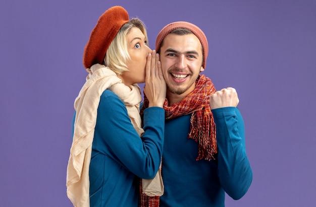 Jeune couple portant un chapeau avec une écharpe le jour de la saint-valentin, une fille suspecte chuchote sur une oreille de gars souriante isolée sur fond bleu