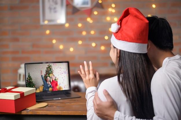 Un jeune couple portant un chapeau de père noël rouge faisant un appel vidéo sur le réseau social avec la famille et les amis le jour de noël.