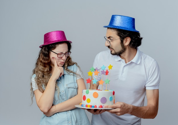 Jeune couple portant des chapeaux roses et bleus guy donne un gâteau d'anniversaire à une fille confuse isolée sur blanc