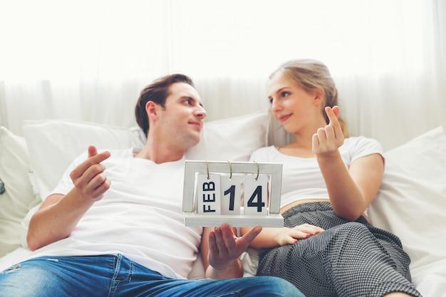 Un jeune couple portant des chemises blanches et se fixant sur le lit, pour célébrer les vacances de la saint-valentin dans la chambre.