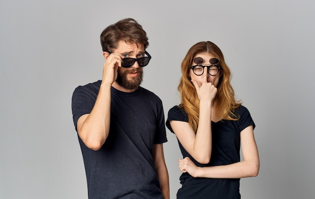 Jeune couple portant des lunettes noires t-shirts noirs style de vie de studio de vêtements décontractés.