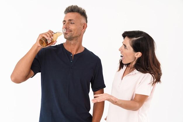 Jeune couple portant une tenue décontractée debout isolé sur un mur blanc, une femme crie après son petit ami pendant qu'il boit de la bière