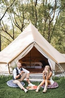 Jeune couple portant des vêtements décontractés boho élégant assis sur les oreillers sur l'herbe verte devant une grande tente wigwam à l'extérieur