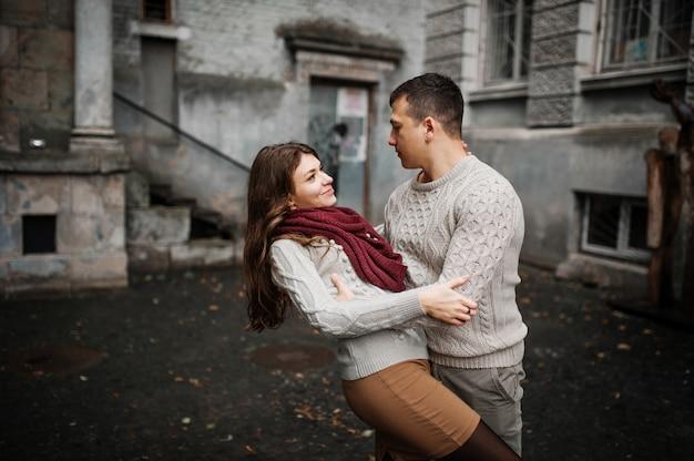 Jeune couple, porter, attaché, chandails chauds, étreindre, amour, vieux, cour, arc, colonnes, ville