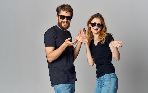 Jeune couple, porter, lunettes noires, t-shirts noirs, vêtements décontractés, studio, style de vie
