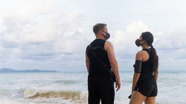 Jeune couple, porter, masque protecteur, debout, plage