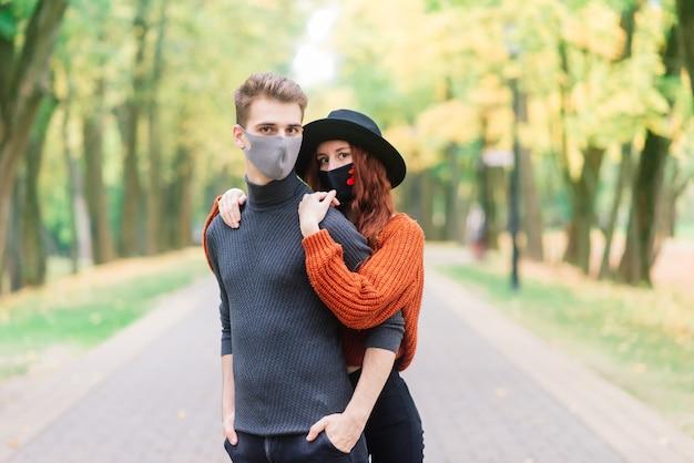 Jeune couple, porter, masques, ensemble, dans parc