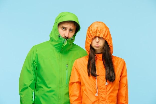 Le jeune couple posant au studio en veste d'automne isolé sur bleu. émotions négatives humaines. concept du temps froid. concepts de mode féminine et masculine