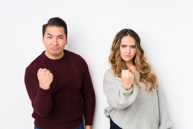 Jeune couple posant sur blanc montrant le poing, expression faciale agressive.