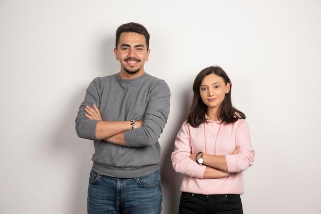 Jeune couple posant les bras croisés sur blanc.