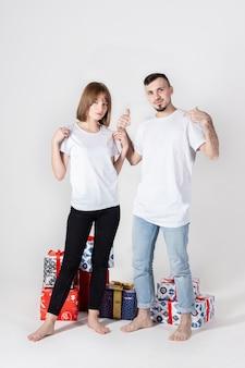 Jeune couple posant avec des cadeaux de noël