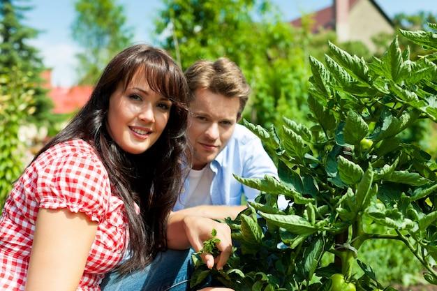 Jeune couple posant dans le jardin
