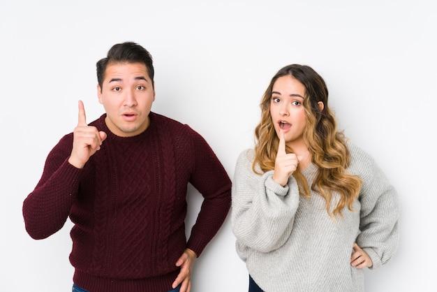 Jeune couple posant dans un mur blanc ayant une idée, un concept d'inspiration.