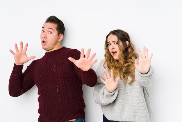 Jeune couple posant dans un mur blanc choqué par un danger imminent