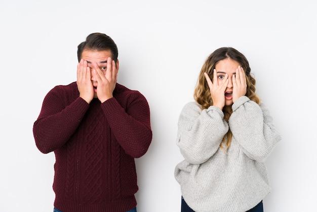 Jeune couple posant dans un mur blanc clignote des doigts effrayé et nerveux.