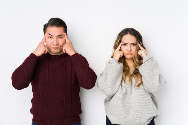 Jeune couple posant dans un mur blanc concentré sur une tâche, gardant les index pointant la tête.